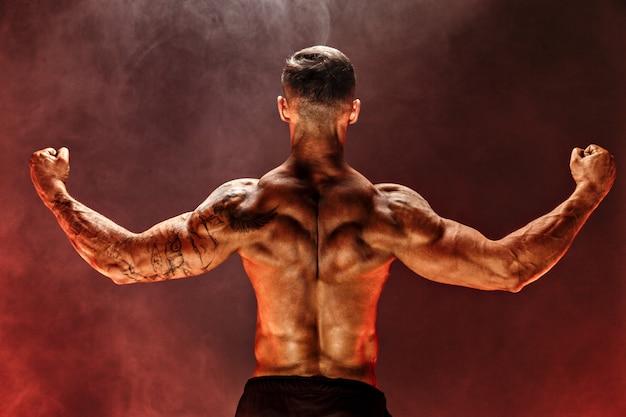 Punto di vista posteriore dell'uomo irriconoscibile, muscoli forti che posano con le braccia giù nel fumo