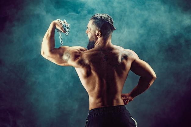 Punto di vista posteriore dell'uomo irriconoscibile, muscoli forti che posano con le braccia giù nel fumo.