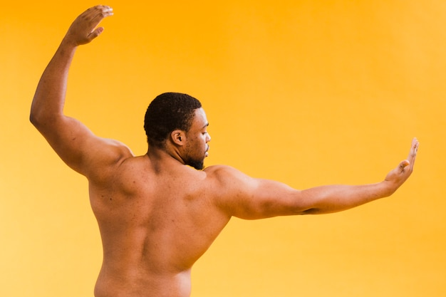 Punto di vista posteriore dell'uomo senza camicia atletico