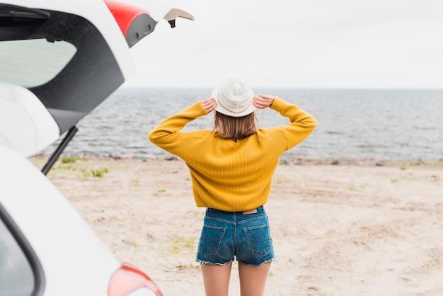 Punto di vista posteriore della donna adorabile che affronta il mare