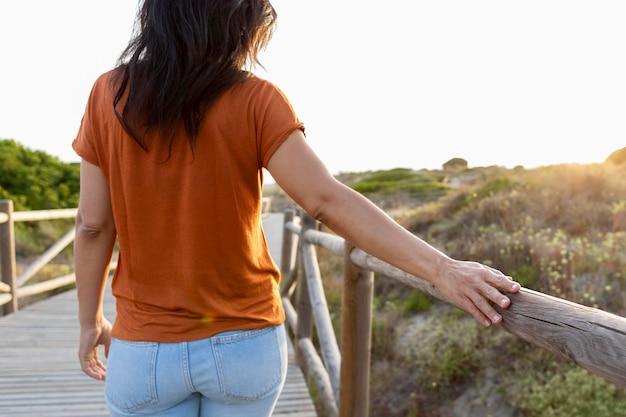 Punto di vista posteriore della donna al sole con il recinto di legno