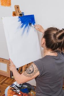 Punto di vista posteriore della donna alla moda che inizia nuova pittura