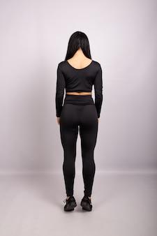 Punto di vista posteriore della donna allegra che indossa leggings sexy
