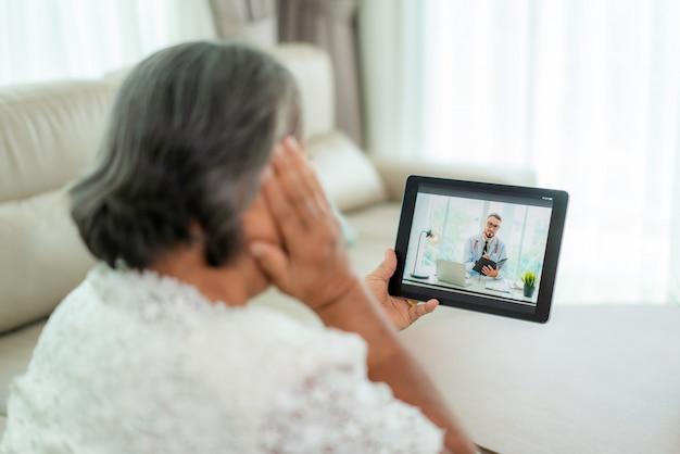 Punto di vista posteriore della donna anziana che fa videochiamata con il suo medico con la sua emicrania di sensibilità sulla consultazione online di servizio di tecnologia digitale di sanità della compressa digitale mentre restando a casa.