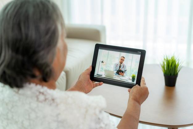 Punto di vista posteriore della donna anziana che fa videochiamata con il suo medico con lei che si sente male sulla consultazione online di servizio di tecnologia digitale di sanità della compressa digitale mentre restando a casa.