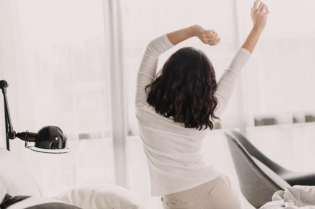 Punto di vista posteriore della donna asiatica nel buongiorno. è seduta e allunga la mano e il corpo.