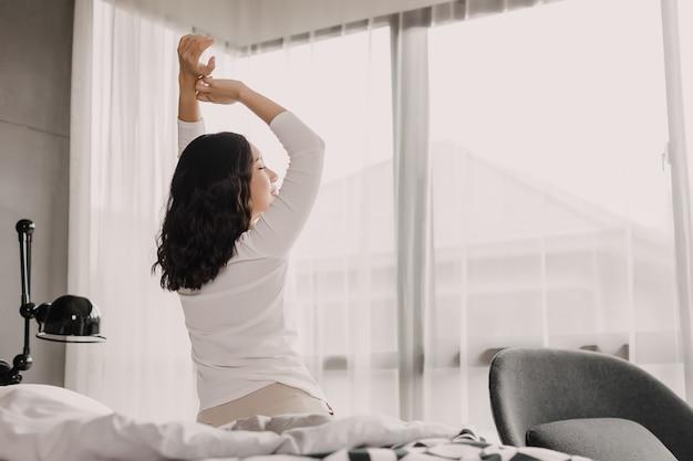 Punto di vista posteriore della donna asiatica nel buongiorno. sorride e allunga la mano e il corpo sul letto