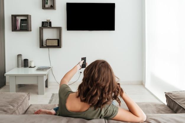 Punto di vista posteriore della donna casuale che si siede sul sofà e che guarda tv nella casa