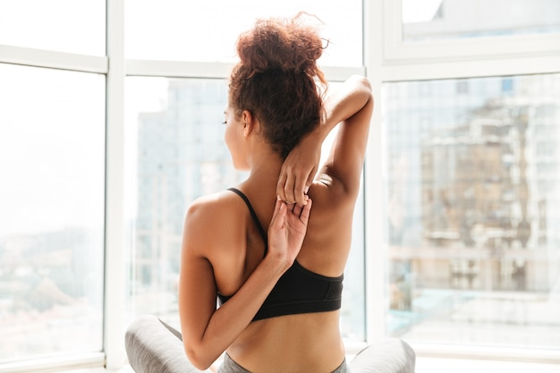 Punto di vista posteriore della donna che allunga le mani prima dell'allenamento