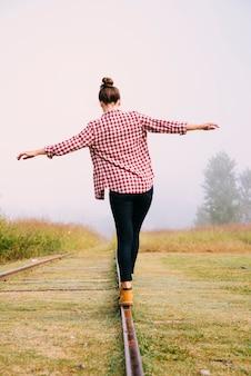 Punto di vista posteriore della donna che equilibra su una ferrovia