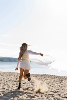 Punto di vista posteriore della donna che funziona sulla sabbia della spiaggia