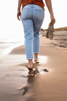 Punto di vista posteriore della donna che gode di una passeggiata sulla spiaggia