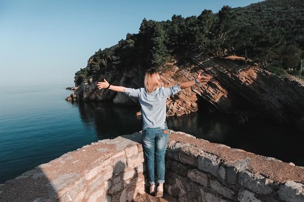 Punto di vista posteriore della donna che pensa da solo e che guarda il mare con l'orizzonte nei precedenti, montenegro