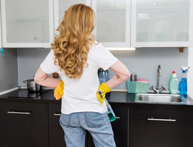 Punto di vista posteriore della donna che pulisce la cucina