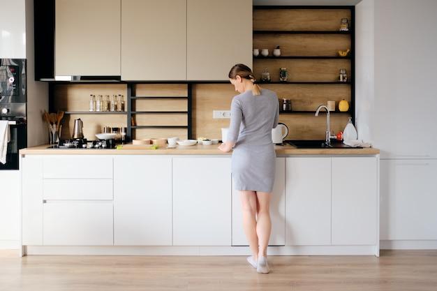 Punto di vista posteriore della donna che sta accanto ad una cucina moderna