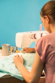 Punto di vista posteriore della donna che usando macchina per cucire