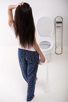 Punto di vista posteriore della donna con carta nella toilette nella mattina.
