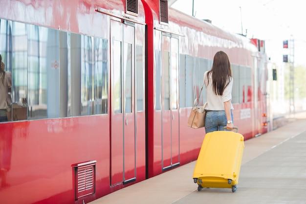 Punto di vista posteriore della donna con la borsa alla stazione che viaggia in treno