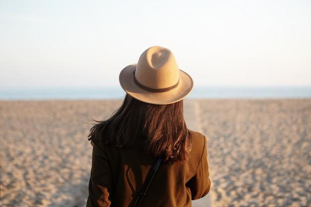Punto di vista posteriore della donna europea in cappello e cappotto che vanno verso il mare sul lungomare nella fresca sera di primavera, sentirsi soli