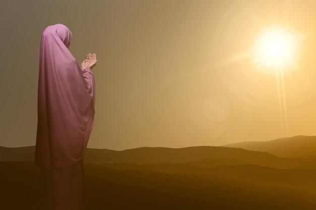 Punto di vista posteriore della donna musulmana asiatica che prega a dio