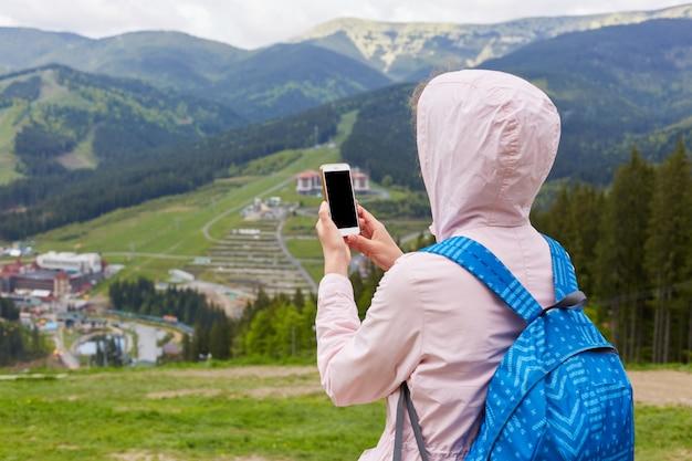 Punto di vista posteriore della donna snella che tiene il suo smartphone in entrambe le mani, scattare foto per il blog di viaggio, in cerca di un nuovo percorso online
