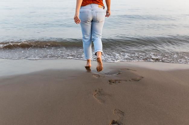 Punto di vista posteriore della donna sulla spiaggia che va nell'acqua