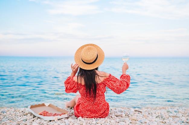 Punto di vista posteriore della donna sulla spiaggia sul picnic con bicchiere di vino e pizza