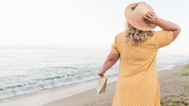 Punto di vista posteriore della donna turistica più anziana alla spiaggia