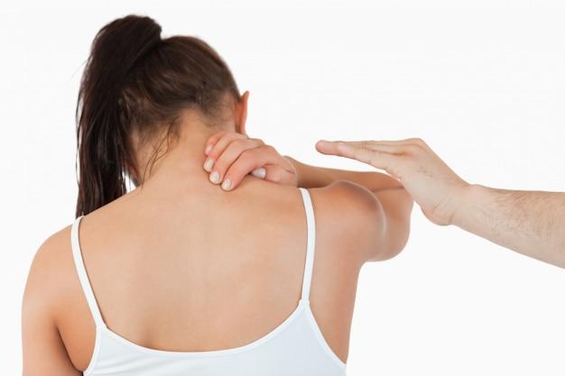 Punto di vista posteriore della femmina che ha dolore nel suo collo