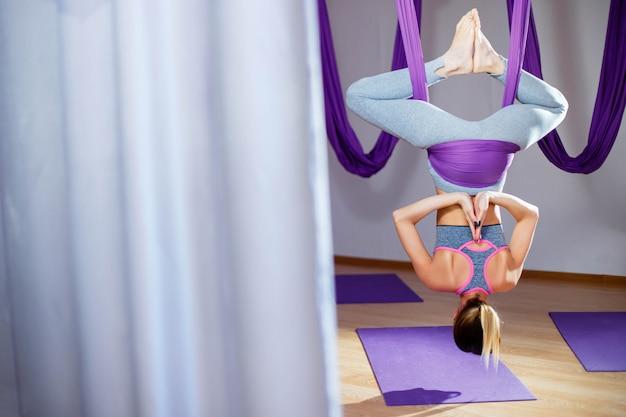 Punto di vista posteriore della giovane donna attraente che fa posa di yoga antigravità