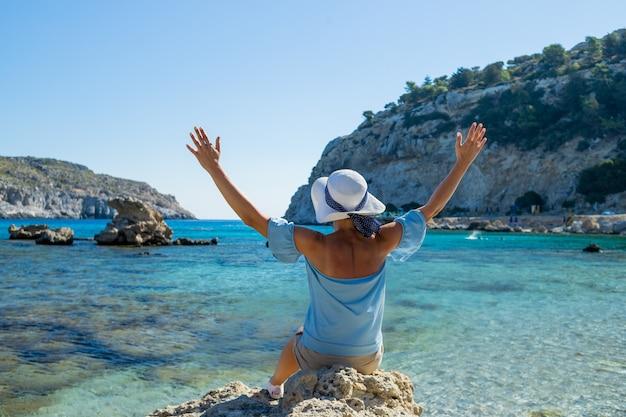 Punto di vista posteriore della giovane donna che estende le armi e che guarda in avanti nella laguna. donna con cappello è blusa blu e cappello bianco, rilassa sulla spiaggia