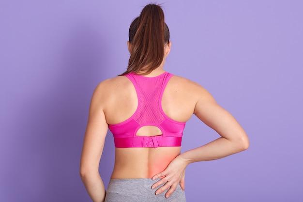 Punto di vista posteriore della giovane donna con dolore alla schiena che sta contro la parete porpora in studio