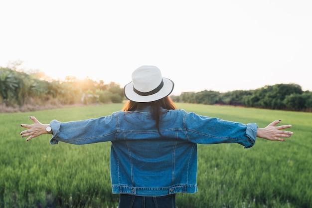 Punto di vista posteriore della giovane donna in cappello ragazza che gode alla bella natura con il tramonto. summ di viaggio