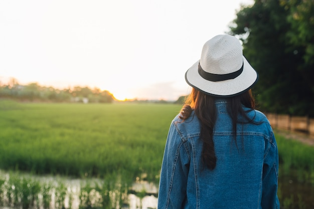 Punto di vista posteriore della giovane donna in cappello ragazza che gode della bellissima natura con il tramonto.
