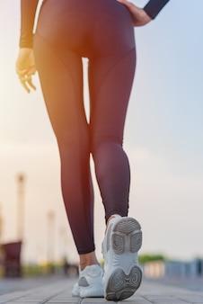 Punto di vista posteriore della giovane donna sexy del corpo in scarpe da tennis sportive all'esterno
