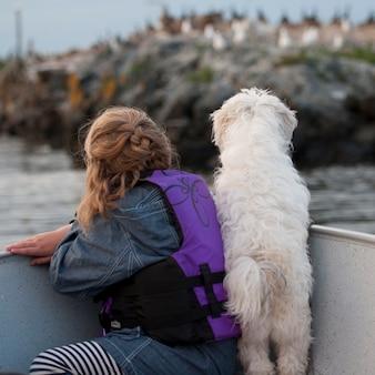 Punto di vista posteriore della ragazza con il suo cane in una barca nel lago of the woods, ontario