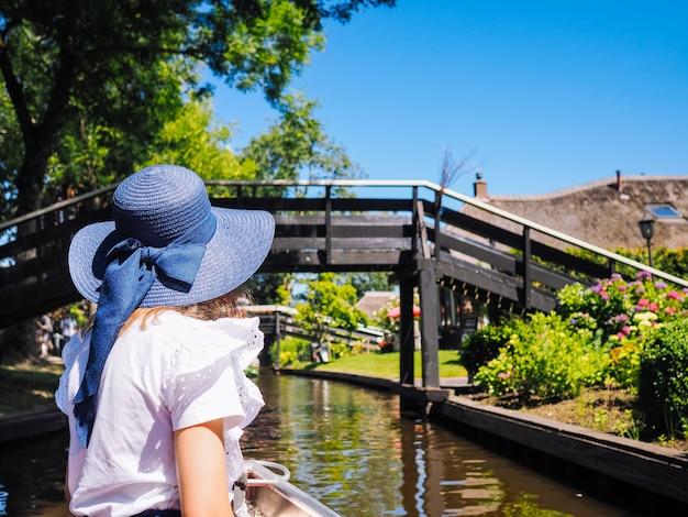 Punto di vista posteriore della ragazza in cappello blu