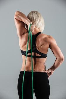 Punto di vista posteriore della ragazza muscolare di forma fisica che allunga con la gomma elastica