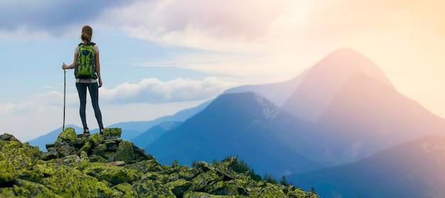 Punto di vista posteriore della ragazza turistica di giovane viaggiatore con zaino e sacco a pelo esile con il bastone che sta sulla cima rocciosa contro il cielo blu luminoso di mattina che gode del panorama nebbioso della catena montuosa. turismo, viaggi e arrampicate.