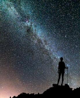 Punto di vista posteriore della ragazza turistica di giovane viaggiatore con zaino e sacco a pelo esile sulla cima della montagna rocciosa sul cielo stellato di notte scura e sulla montagna nebbiosa