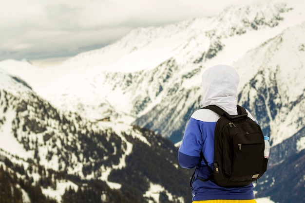 Punto di vista posteriore della viandante turistica in vestiti caldi con lo zaino