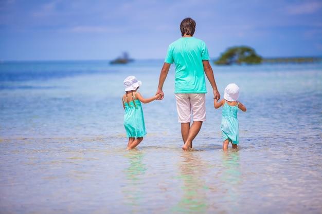 Punto di vista posteriore delle bambine adorabili e del giovane padre che camminano all'isola esotica