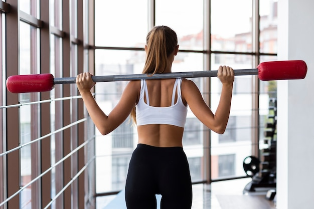 Punto di vista posteriore di addestramento della donna con la barra dei pesi