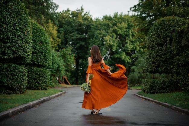 Punto di vista posteriore di bella donna in vestito arancio lungo che cammina sulla strada bagnata