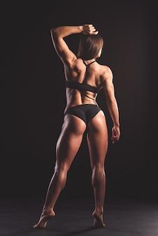 Punto di vista posteriore di bella donna muscolare forte.