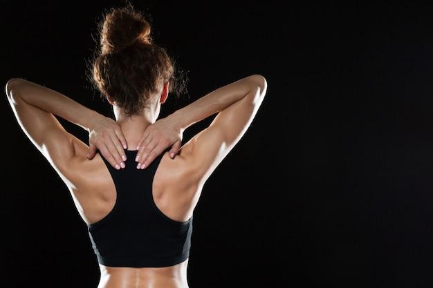 Punto di vista posteriore di forte donna di forma fisica che posa nello studio