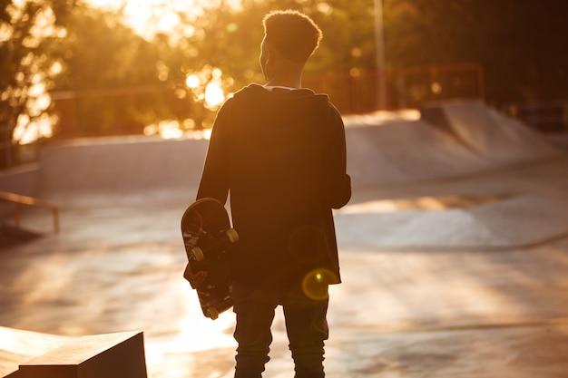 Punto di vista posteriore di giovane adolescente maschio africano con le cuffie