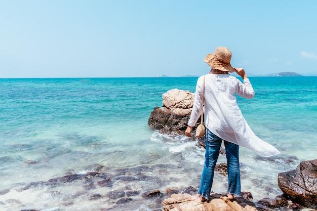 Punto di vista posteriore di giovane donna asiatica musulmana che guarda dalla scogliera. futuro e concetto di ricerca. donna felice con le mani in alto in piedi sulla scogliera sul mare. atmosfera di viaggio, concetti di vincitore, libertà.