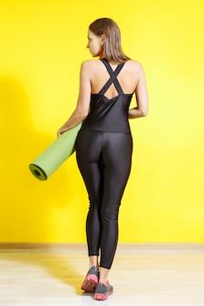 Punto di vista posteriore di giovane donna sportiva che tiene una stuoia di yoga