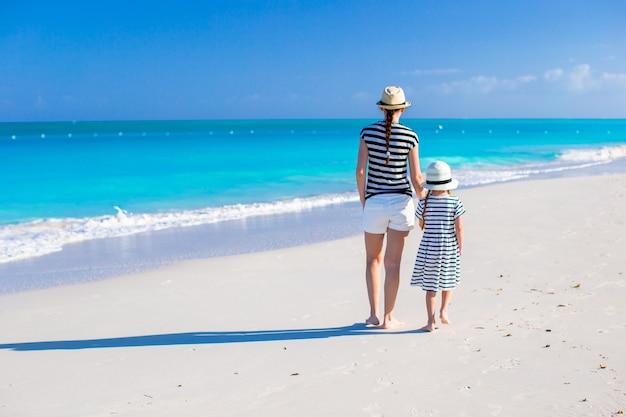 Punto di vista posteriore di giovane madre e piccola figlia alla spiaggia caraibica